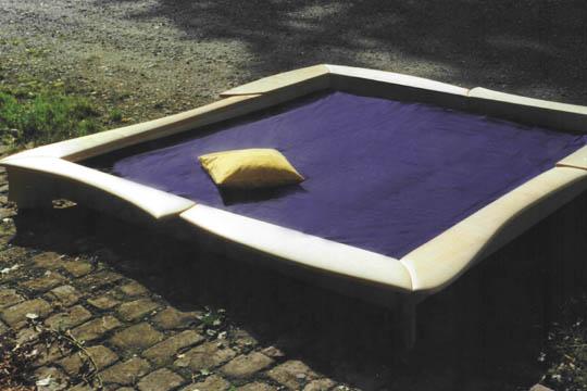 Bett aus Ahorn mit einer Umrandung in geschwungenen Formen. Konvexe und konkave Flächen vermitteln ein besonderes, sinnliches Gefühl.