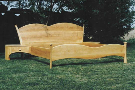 Ein Bett aus Erlenholz. Die angebauten Nachttischchen nehmen die ausladende Shwingung des Kopfteils auf.