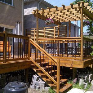 Create separation between your home and a nearby neighbor with a horizontal fence, platform deck and raised pergola. The stylish deck offers multiple areas for relaxing and entertaining and a beautiful spot for hanging flowers.