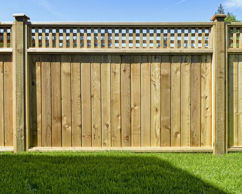 Elevate an ordinary cedar privacy fence by adding decorative capped posts in between the panels and a striking square lattice panel on top.