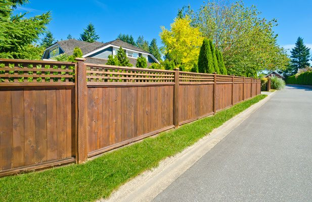 This street-lined fence offers grace and beauty on the inside and outside. Accent a cedar lap board fence with a square lattice top to increase the visual appeal.