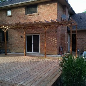 Add character to an expansive platform deck with a sun-shading pergola. Drape the structure in vines to shield the sliding glass doors and brick exterior from the weather.