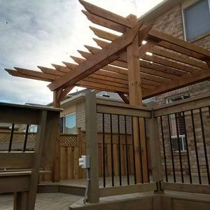 Break up a bland two-story brick home with an elevated pergola featuring chunky posts and staggered board lengths.