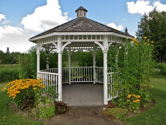 Anchor your garden with a classic gazebo wrapped in simple fence railings, posts and arches and then topped with an ornate peak for added character.