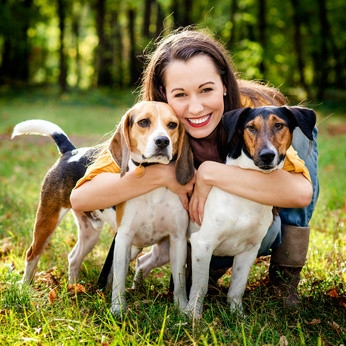 junge Frau umarmt zwei Hunden
