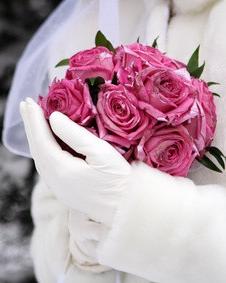 Braut mit Rosenstrauß im Schnee
