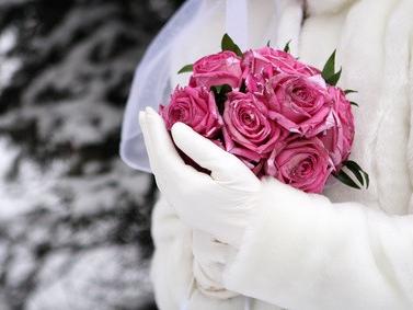 Braut mit Rosenstrauß im Winter