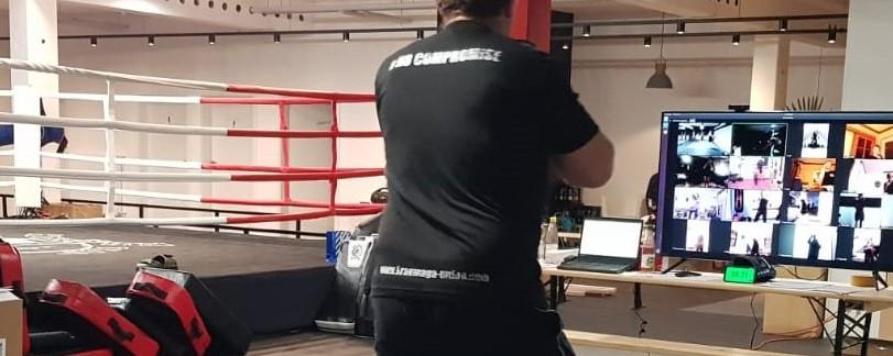 Ein TKC-Trainer leitet ein interaktives Online-Training im Gym. Die Teilnehmer sind über den Bildschirm zugeschaltet und werden vom Trainer individuell und direkt z.B. korrigiert.
