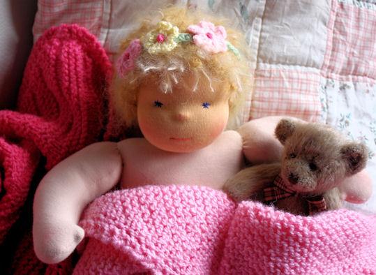 Diese Puppe wartet warm eingepackt in Decken auf ihre neuen Kleider