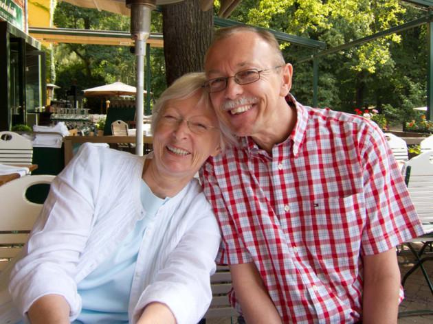 Zwei Personen sitzen im Gartenrestaurant und lehnen aneinander. sie lächeln in die Kamera: links die Illustratorin Petra-Ines Kaune mit einem hellen Jäckchen, rechts Autor Peter Bach jr. im rotkarierten kurzärmeligen Hemd.