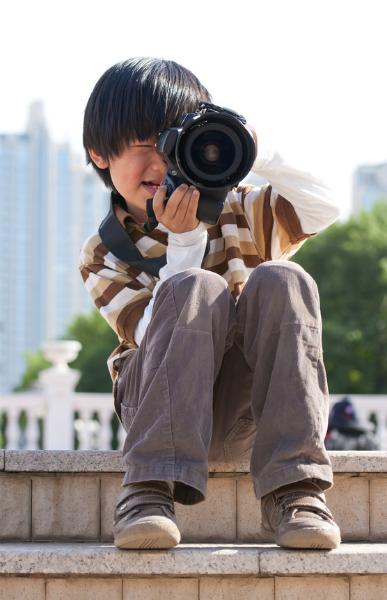 Kind in einer Stadt, das auf einer Treppe sitzt und fotografiert