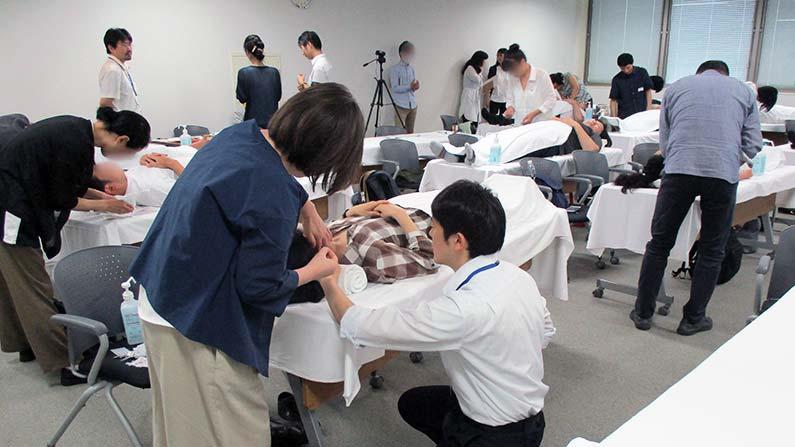 中医鍼灸ー刺鍼方向について吉田先生の指導を受ける研修生