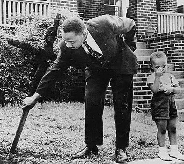 Martin Luther King e suo figlio rimuovendo una croce bruciata che membro del KKK lasciarono di fronte a casa sua nel 1960