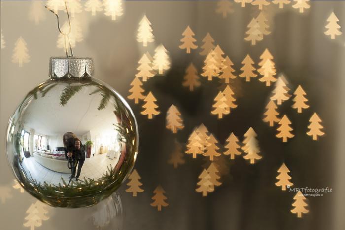 Detail opname van een kerstbal in de boom met reflectie van mijn persoontje plus een Bokeh figuurtje