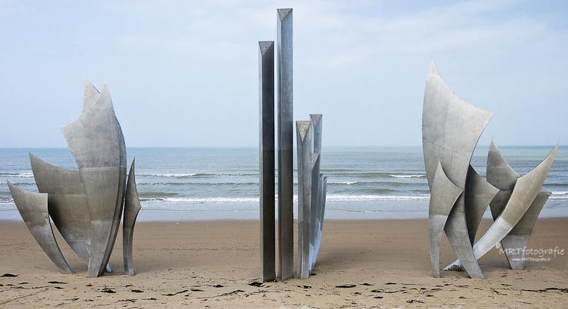 Het monument Les Braves aan het strand van de Normandisch kust lijkt symmetrisch maar door het verschil in het rechter en linker onderdeel is het dat niet.
