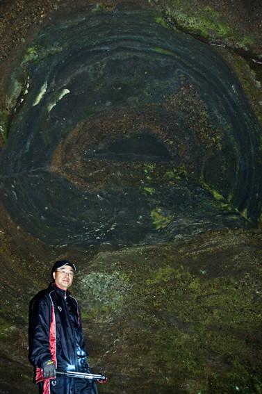 洞窟の正面に年輪のような模様の地層がある(鳥谷部氏)。巨木の珪化木なのか、地層なのかを調べました。