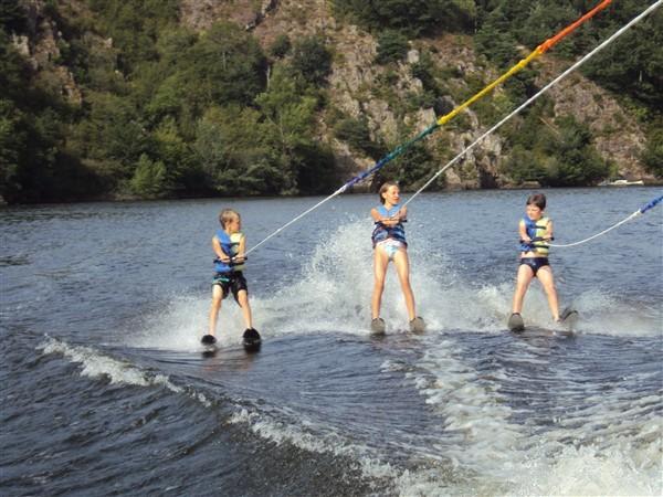 trois jeunes skieurs tractés en bi-ski