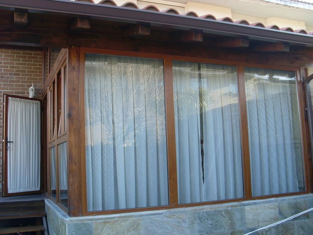 Porche de madera con ventanales fijos