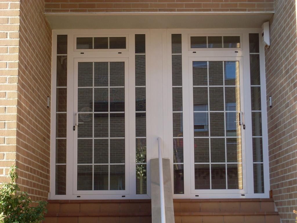 Puerta de portal con vidrio de barrotillo