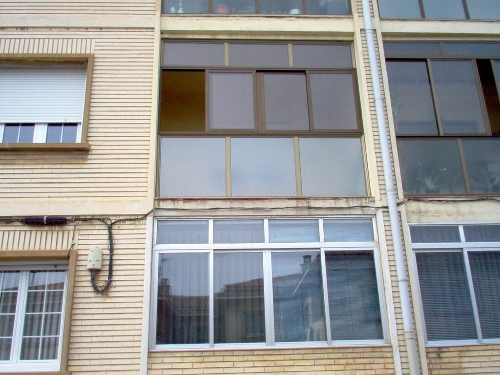 Cerramiento de terraza con ventanas correderas en color bronce