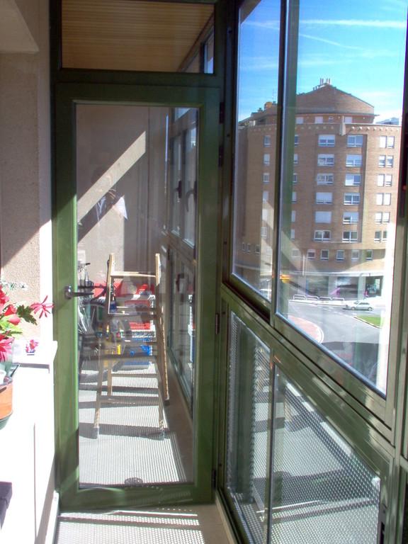 Cerramiento de terraza con ventanas correderas y puertas abisagradas