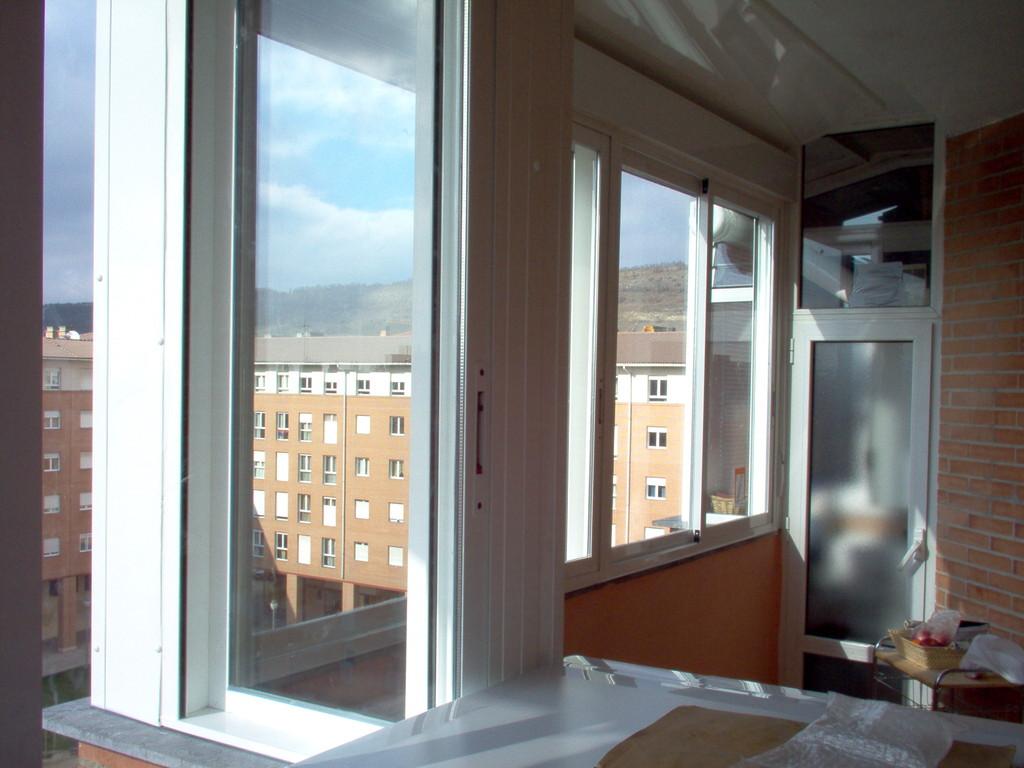 Cerramiento de terraza con ventanas correderas y persianas