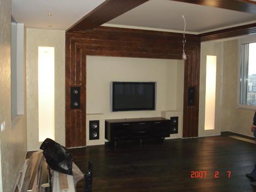 Домашний кинотеатр, в квартире, спроектированный конструктив для встраиваемой акустики и моторизированного видео-экрана, который опускается из ниши.