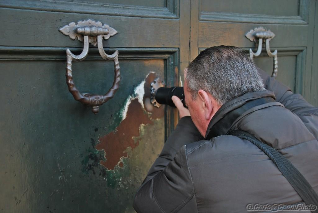 Turista mentre tenta lo scatto dal buco della serratura