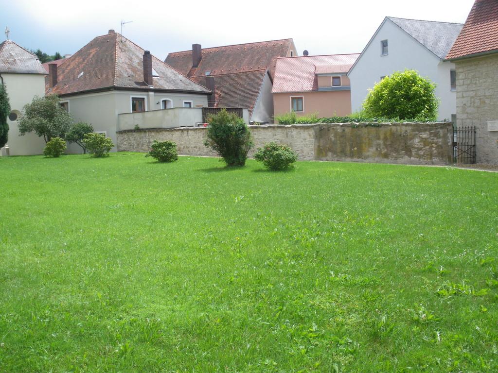 Neugestalteter Weg an der alten Friedhofsmauer. Friedhof wurde 1860 aufgelöst.