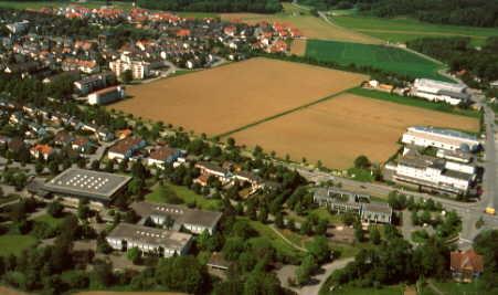 Im Vordergrund ist das Schulhaus und links daneben die Sporthalle.