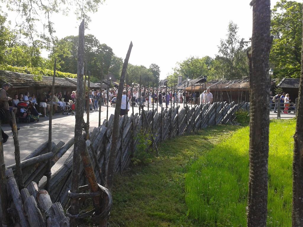 塀の向こうに見える大勢の人と屋台