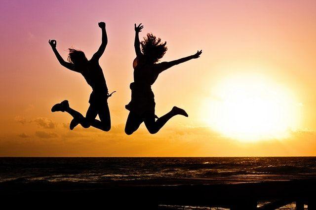 Auf dem Bild springen zwei Menschen am Strand mit Freude in die Luft. Für mehr Informationen die Bildunterschrift lesen.