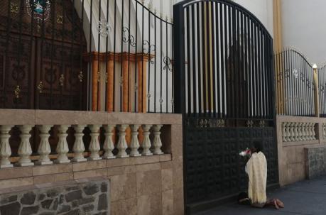 Mujer reza frente a una Iglesia cerrada en Ambato, Ecuador. Foto: Fabián Maisanche / EL COMERCIO
