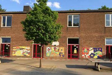 Blick auf das von Kindern gestaltete Mosaik auf dem kleinen Schulhof am OGS Gebäude