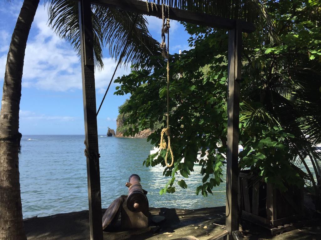 """Galgen und Kanone: Originalrequisiten aus """"Fluch der Karibik"""" - im Hintergrund der Steinbogen, in dem im Film die Piraten aufgeknüpft waren"""