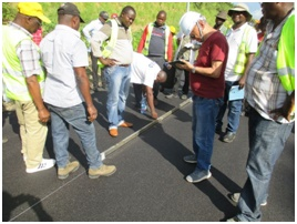 舗装施工管理のOJT研修。アスファルト舗装後の平坦性を確認しているところ。