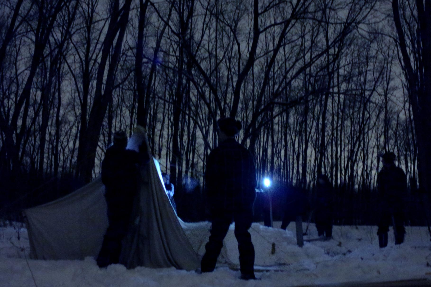 Les éclaireurs en camp d'hiver, montant leur campement à la lueur des lampes de poche