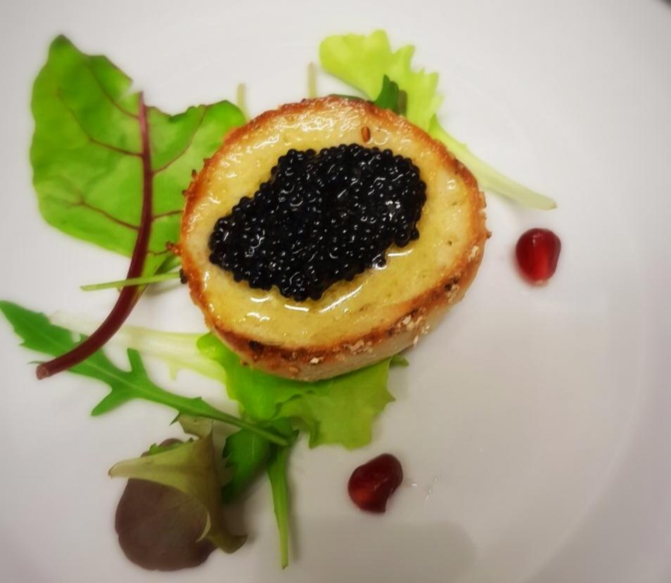 Hausgemachtes Brotcrostino mit Kaviar auf Babysalat mit Granatapfel