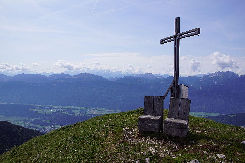 Gipfelkreuz mit Sitzplätzen und Karnischen Alpen im Hintergrund
