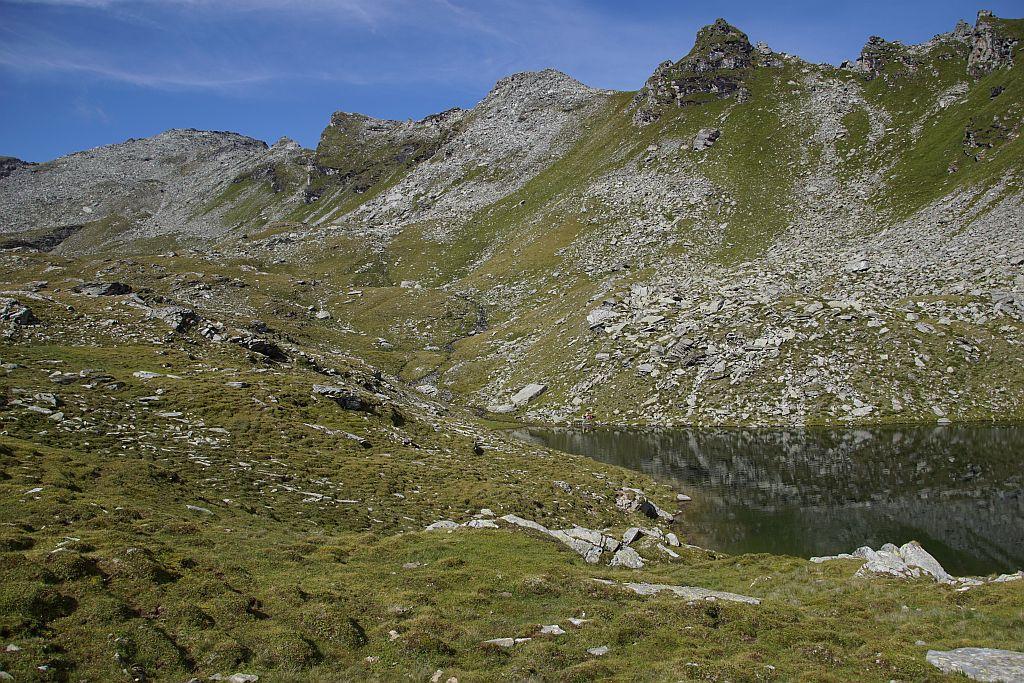 Der See ist erreicht, links im Bildhintergrund ist schon der Gipfel zu erkennen. Der Aufstieg dorthin erfolgt zunächst über Almgelände, dann durch eine Rinne und schließlich über Blockwerk zum Gipfel