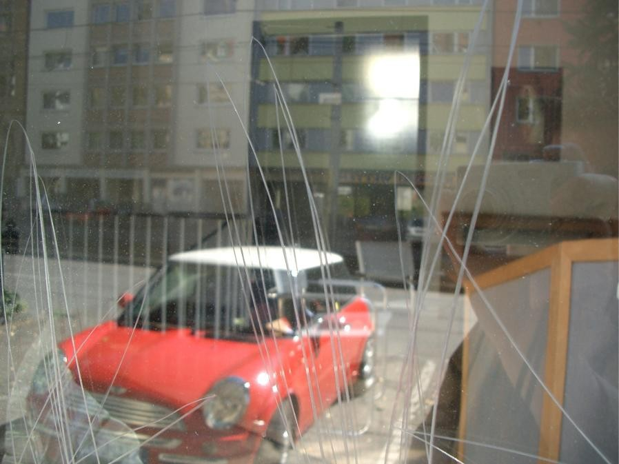 Glaskratzer durch Vandalismus - Nahaufnahme mit rotem Auto