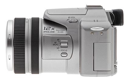 Il lato opposto della fotocamera è dotato dell'altro occhiello della cinghia del collo, nonché il quadrante di regolazione diottrica nascosto sul lato del mirino ottico elettronico. Un interruttore a scorrimento a scorrimento sul lato della barra.
