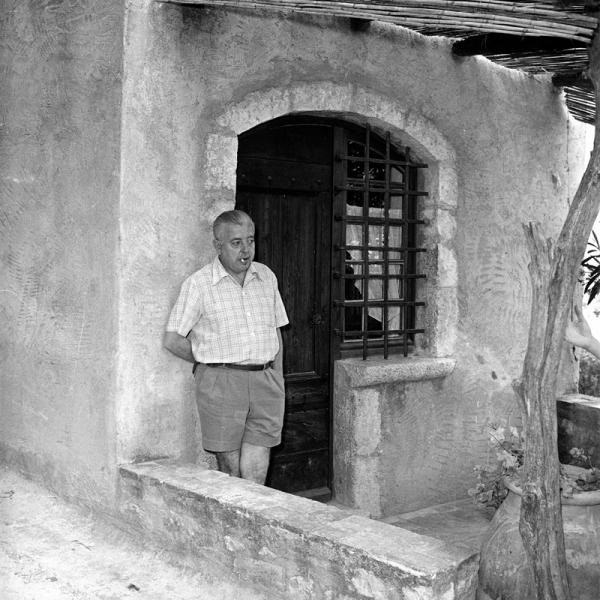"""JACQUES PREVERT DEVANT """"LA MIETTE"""" SA MAISON AU COEUR DE SAINT-PAUL-DE-VENCE où IL S'INSTALLA EN 1948 APRES UN GRAVE ACCIDENT. PAR LA SUITE IL IRA  AVEC JANINE et LEUR FILLE MINETTE  à """"L'ORMEAU"""" UNE VILLA  à L'EXTERIEUR DU VILLAGE. C* JACQUES GOMOT."""