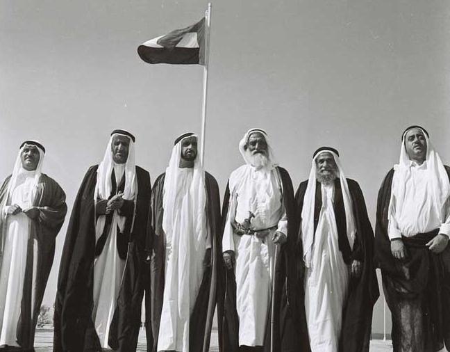 2 DECEMBRE 1971. SOUS LE DRAPEAU DE LA FEDERATION. A g. L'EMIR KHALID BIN MUHAMMAD AL QASIMI. L'EMIRAT DE RAS AL KHAIMAH REJOINDRA LA FEDERATION EN FEVRIER 1972