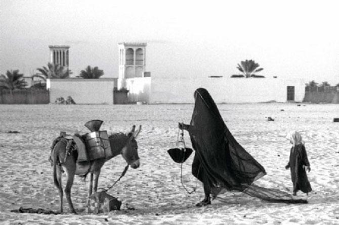 Une femme puisant de l'eau à l'extérieur du Fort Qasr el Horn