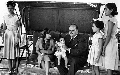 1952.ROME. LA PRINCESSE FADIA DEBOUT A COTE DE SON PERE ROI FAROUK Ier TENANT LE ROI FOUAD II DANS SES BRAS.