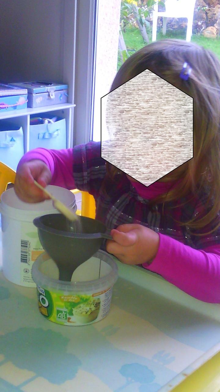 atelier type Montessori : remplir à l'aide d'une cuillère et d'un entonoir