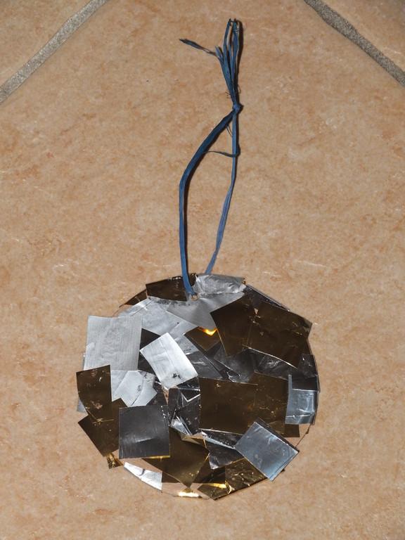 rond en carton recouvert de colle, puis l'enfant y place des morceaux de papier brillant