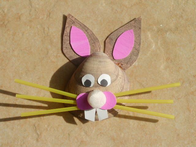 tête de lapin de Pâques avec un gros coquillage peint, des paillles et du carton
