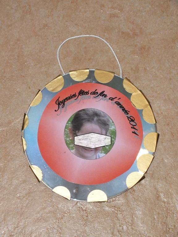 boule de Noël avec 2 CD collés avec une ficelle en leur centre, puis déco avec photo et gommettes